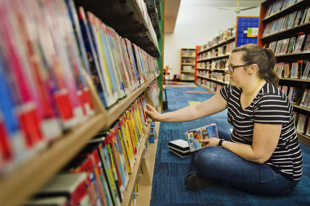 Library worker placing items on shelves at Grace A. Dow library